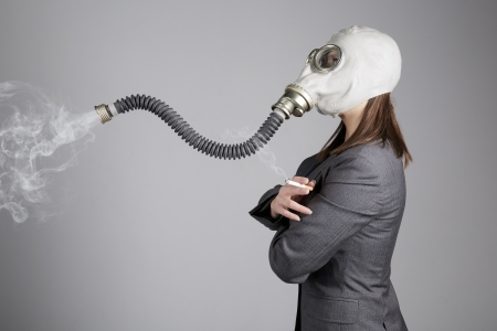 Woman in a gas mask with a cigarette  photo