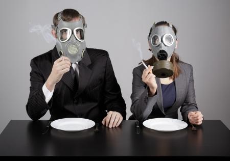 dangerous ideas: Couple at gas masks burning cigarettes  Stock Photo