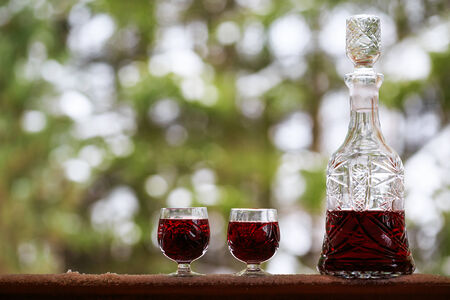 Decanter and wineglasses of red wine outdoors  photo