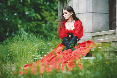 Woman in red Victorian dress sitting on stairs photo