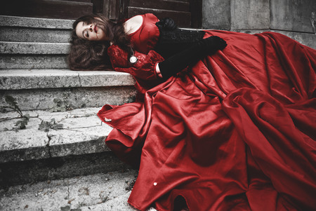 Lying and bleeding woman in a red Victorian dress