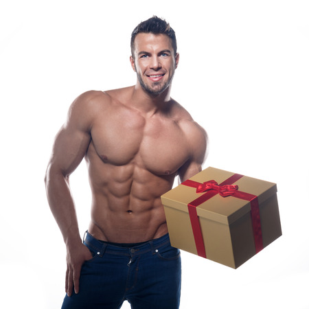 Muscular sexy man with a gift on a white background  Stock Photo