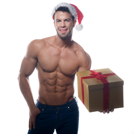 Muscular, sexy santa claus with gift on white background