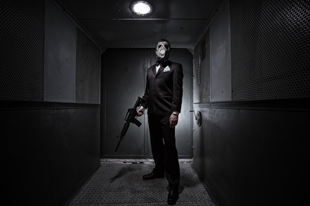 assasin: Male with the rifle and gas mask in an old elevator Stock Photo