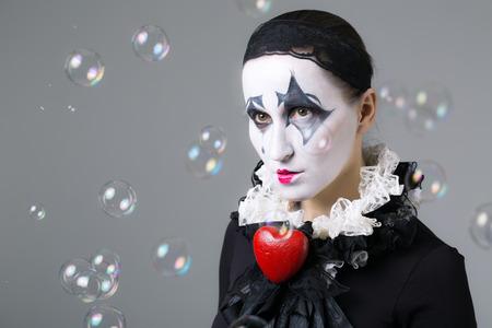 arlecchino: Donna in arlecchino mascherato con bolle di sapone in background Archivio Fotografico