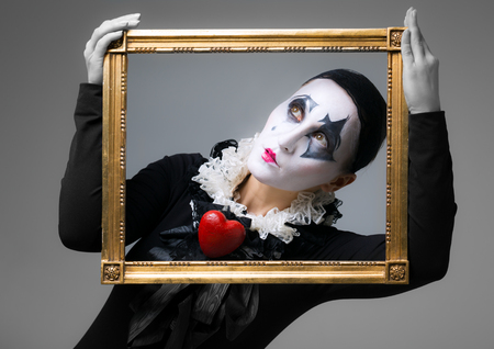 harlequin clown in disguise: Woman in disguise harlequin in the picture frame Stock Photo