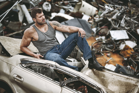The man taking a rest on a car wreck