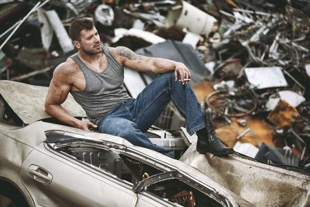 scrapheap: The man taking a rest on a car wreck
