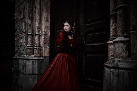 Mysterieuze vrouw in rode Victoriaanse jurk met een kaars