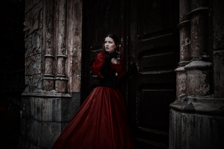 Mysterious woman in red Victorian dress with a candle Reklamní fotografie - 47599214