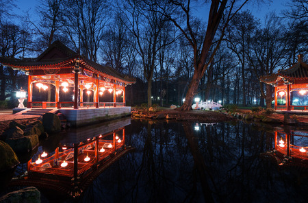 lazienki: Traditional Chinese pavilions in Lazienki Park in Warsaw at night Editorial