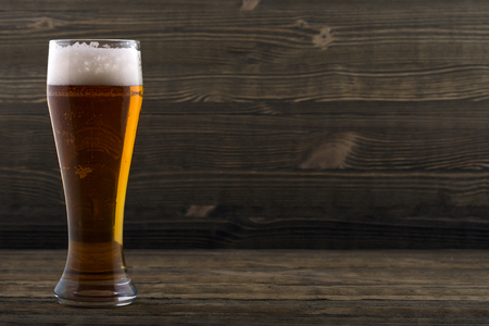 unwholesome: Glass of beer on a wooden countertop Stock Photo