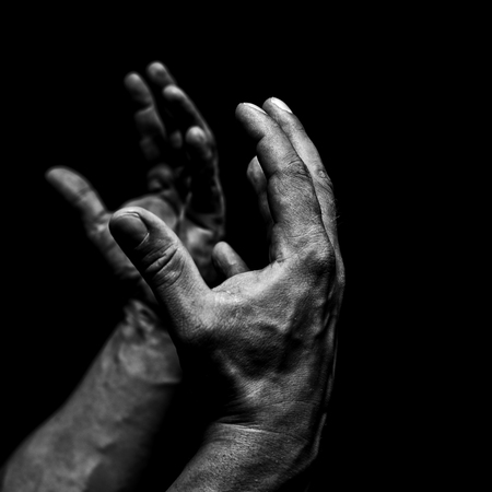 plead: Mens hands on a black background