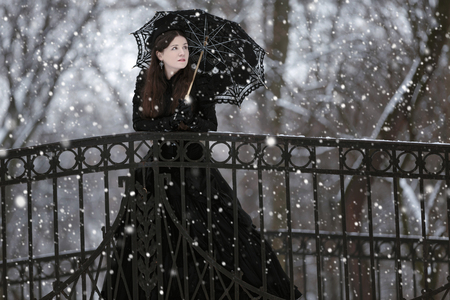 sunshade: Woman in black Victorian dress in the winter park