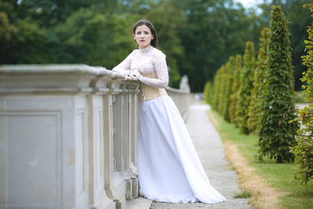 Woman in white Victorian dress in spring park Stock Photo