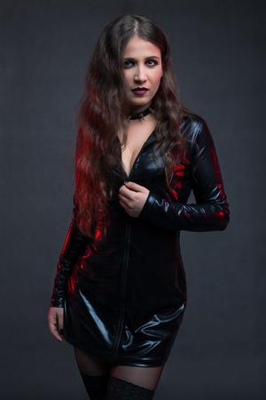 Sexy girl in latex dress in studio