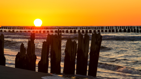 groynes: Sunset over the Baltic Sea against the background of old wooden breakwaters Stock Photo