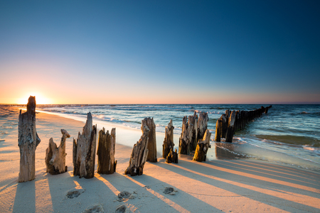 groynes: Sunset on the Baltic Sea beach and old wooden breakwater
