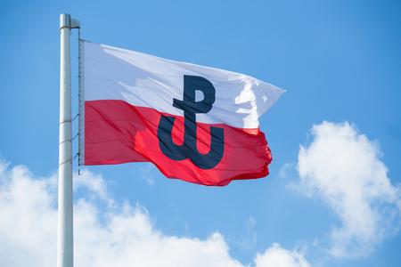 Polnische Flagge mit dem Symbol der polnischen Kämpfe. Symbol des Warschauer Aufstandes 1944 Standard-Bild