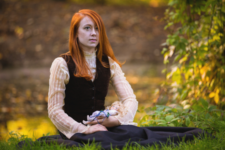 Red-haired woman in Victorian outfit with autumn park