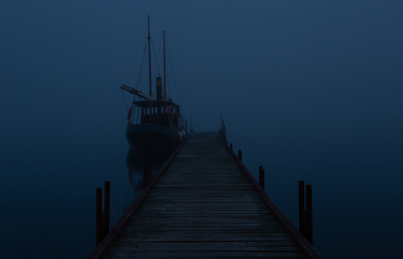 Boat at the pier in time of fog by night Stock fotó