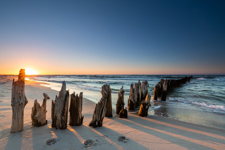 Wooden breakwater at sunset on the Baltic Sea Standard-Bild - 121820917