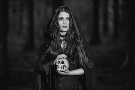 Portrait of a witch with a skull