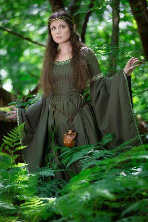 Femme elfe vêtue d'une robe verte dans la forêt