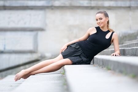 Beautiful woman with shapely long legs in a black skirt