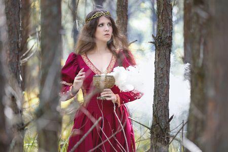 Mujer en un vestido rojo lanzando un hechizo con humo