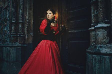 Mysterieuze vrouw in een rode Victoriaanse jurk bij de oude deur
