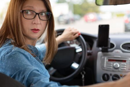 A woman driving the car backwards Foto de archivo