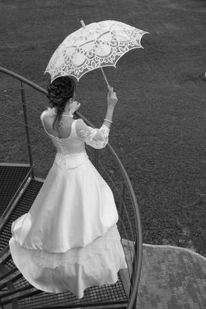 Black and white photo. Bride with umbrella waiting for her beloved.  photo