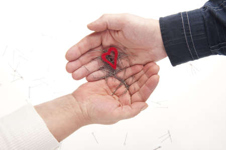 relational: Two hands, heart and needles symbolising crisis in relationships Stock Photo