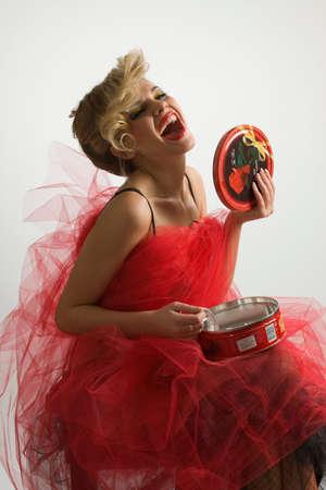 サプライズ プレゼントを赤い透けて見えるスカートの中の美しい女性 写真素材