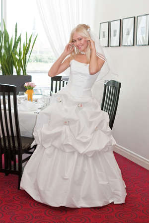 Beautiful blonde bride in white dress in interior photo