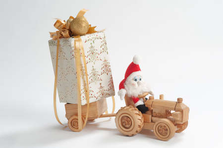 dwarfs: Gnome driving toy tractor with christmas present in trailer