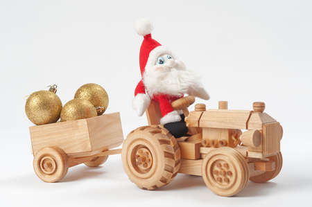 dwarf christmas: Gnome driving tractor with christmas toys in trailer Stock Photo