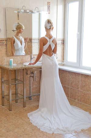 Beautiful blonde bride looking in the miirror. photo