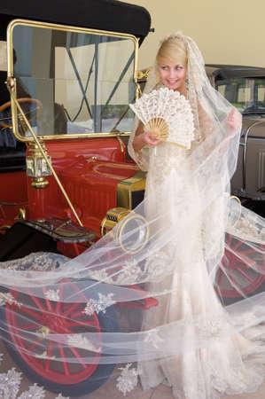 ファンに立って次のアンティーク車と美しい花嫁。