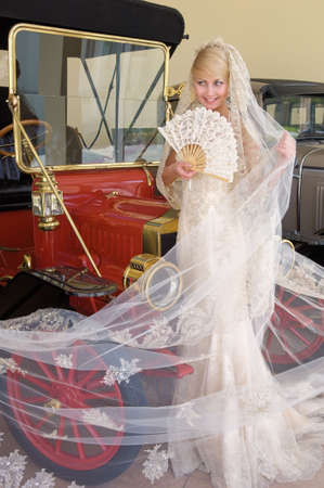 Beautiful bride with fan standing next antique car. photo