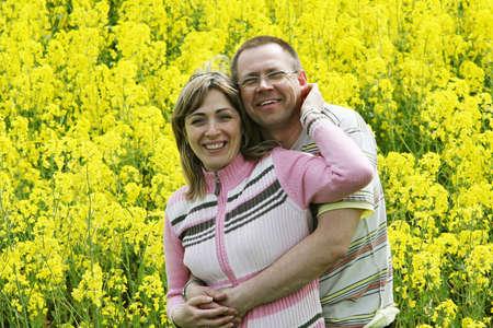 ハッピーと笑顔の花の草原で中年のカップル。 写真素材
