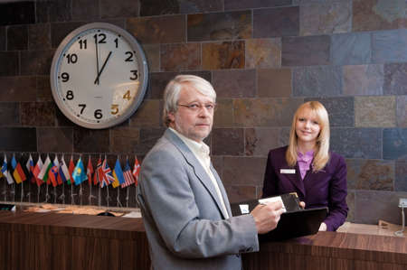 checking in: Businessman checking in at the reception desk