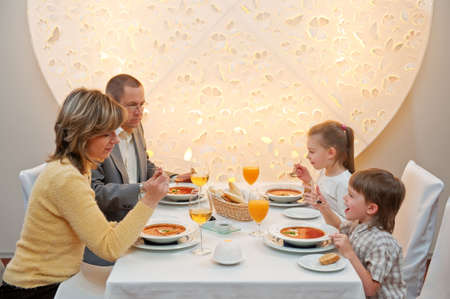 Happy family enjoying meal sitting at restaurant table photo