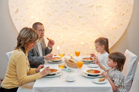 レストランのテーブルに座って食事を楽しんで幸せな家族