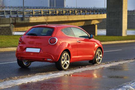 赤い車が橋、リガ、ラトビアの横都市で駐車