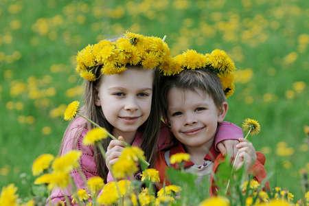兄と妹はタンポポの牧草地の夏の時間をお楽しみください。