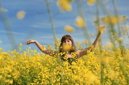 adult rape: Young happy woman on summer day in the flower meadow and blue sky at the background.