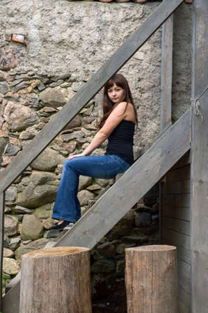 Young beautiful woman sitting on the stairs.  near old castle ruins. photo