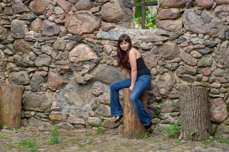 Young beautiful woman sitting on the log near old castle ruins.  photo